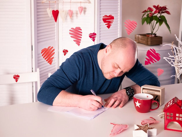 Man sitting and writing a love letter to his sweetheart on lovely light interior with hearts flying around him.