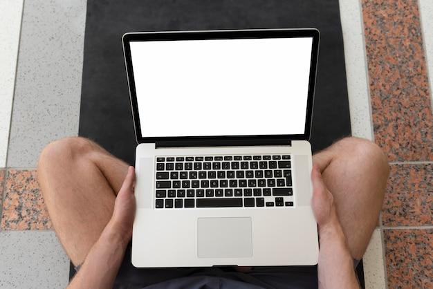 Man sitting on yoga map using laptop