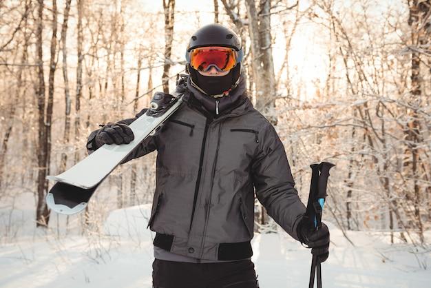 Uomo in abbigliamento da sci che tiene gli sci sulla spalla