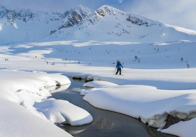 昼間は雪で覆われた山でスキーをする男性