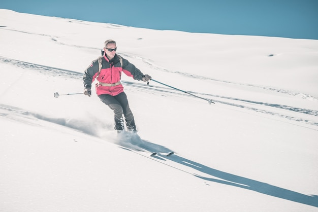 Man skiing off piste on snowy slope in the italian alps