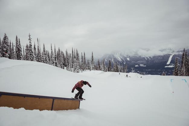 Человек, катающийся на лыжах на снежных альпах на горнолыжном курорте