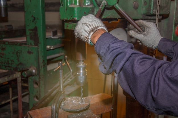 A man skilled working factory welder, cutting, grinding, drill