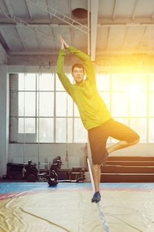 Человек расслабляется, гуляя и балансируя на веревке, слеклайн в спортивном зале