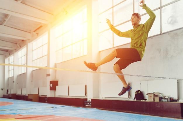 Man slacklining walking and balancing on a rope, slackline in a sports hall