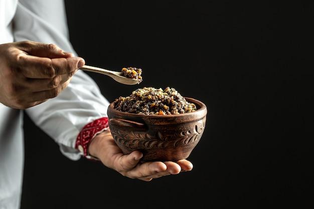 Man in slavic shirt holding bowl with traditional kutia