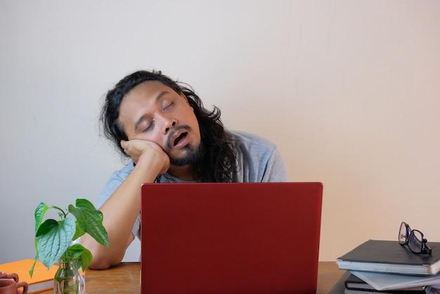 男は前のラップトップで寝る