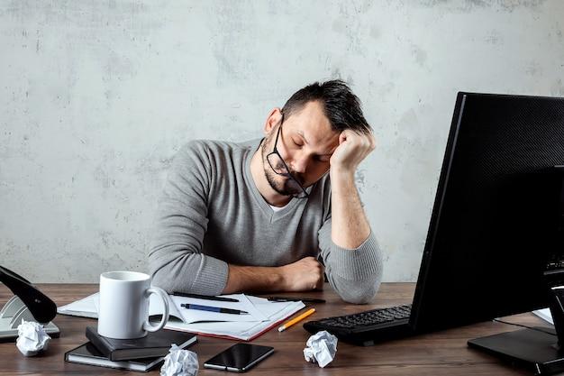 남자는 사무실에서 테이블에서 자 고입니다. 사무, 많은 일, 피로, 게으름의 개념. 공간을 복사하십시오.