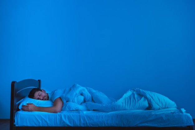 The man sleeping on the bed. evening night time