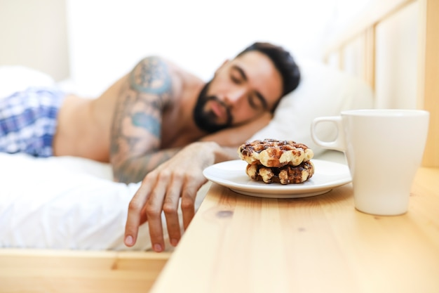 Man sleeping on bed with sweet food and cup of coffee over wooden desk