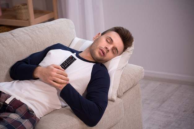 Man sleeping on couch with tv remote in his hands.