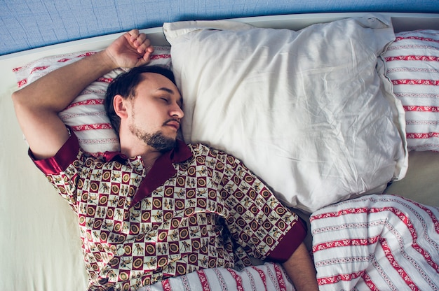 Man sleeping in his bed on white pillow