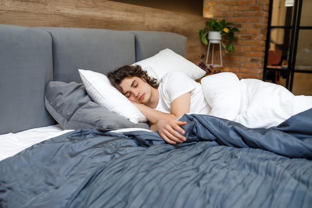 柔らかな日光の下でベッドで寝ている男