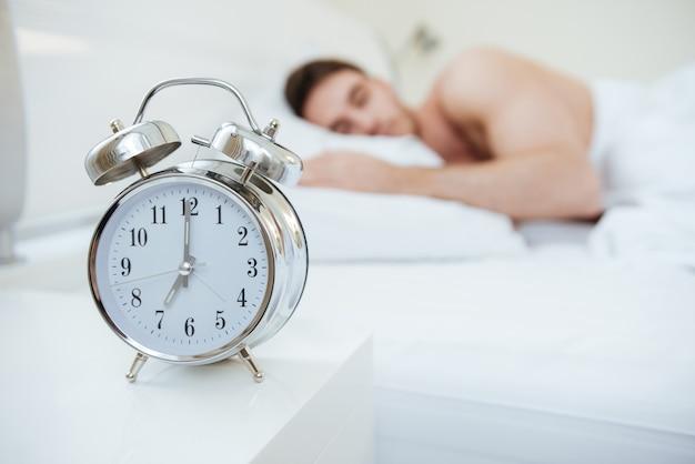 Человек спит на кровати. сосредоточьтесь на часах, которые на тумбочке возле кровати.