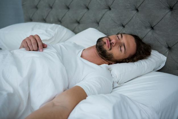 Человек спит на своей кровати