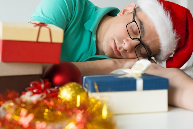 Man sleeping on table with christmas gifts and baubles