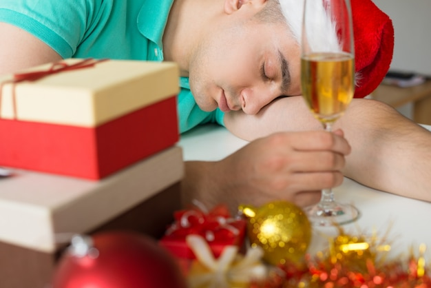 Man sleeping on table with christmas gifts and champagne glass