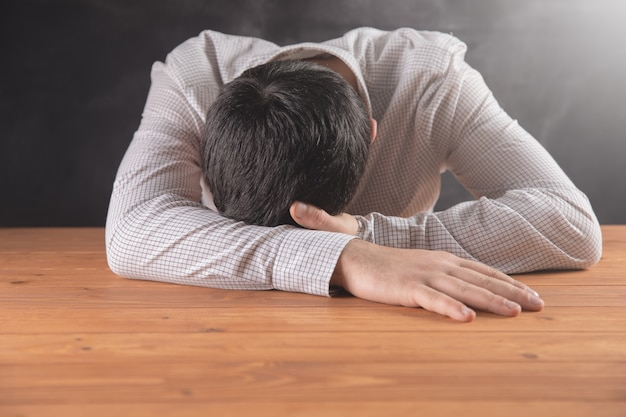 Man sleeping on a wooden table .