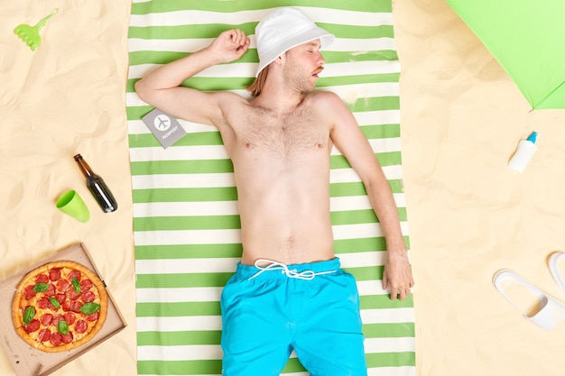 Man sleeps at beach snorkels and sees sweet dreams lies in sun wears sun hat shorts surrounded by pizza beer sunscreen and slippers being on holiday during summer time