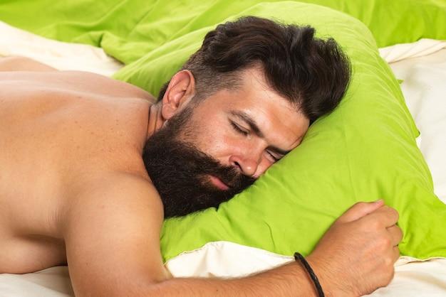 남자는 매우 깊은 잠으로 침대에서 잔다.