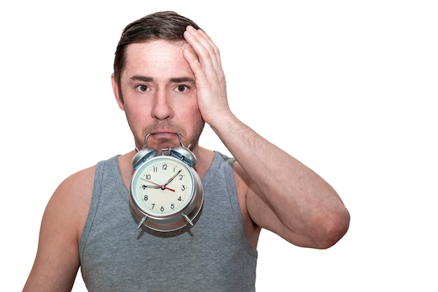 The man slept for work. a man holds an alarm clock in his teeth. puzzled facial expression. holds his head with his hand. isolated white background.