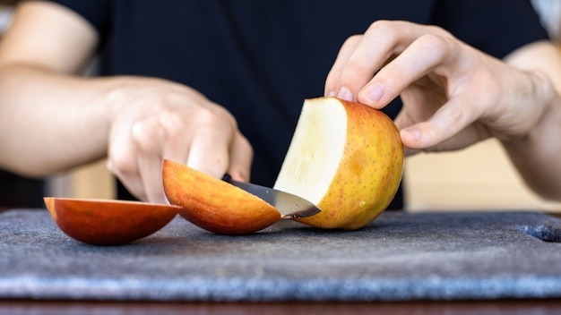 A man slicing apple on a cooking board using a knife