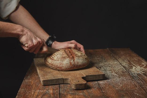 暗い背景の上の木の板に新鮮な有機パンをスライスする男