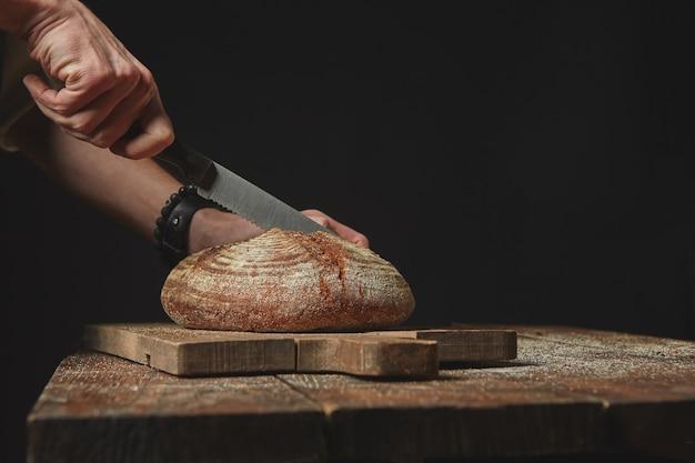 木の板に焼きたての有機パンをスライスする男