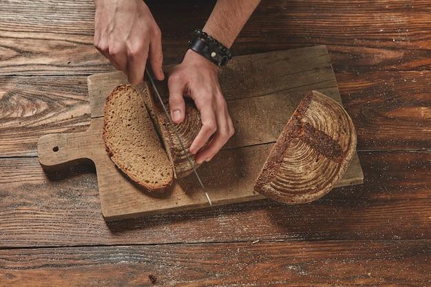 木製の茶色の背景に焼きたての有機パンをスライスする男フラットレイ