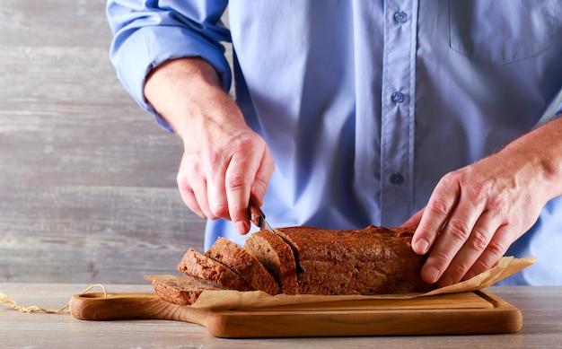 Мужчина нарезает свежеиспеченный банановый хлеб из цельной еды