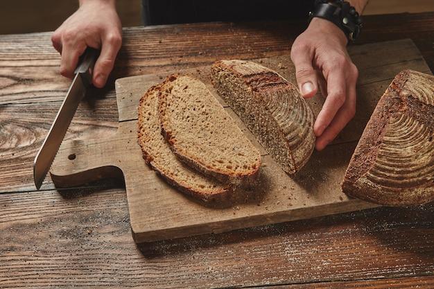 おいしい新鮮なライ麦パンをスライスする男健康的な食事の概念