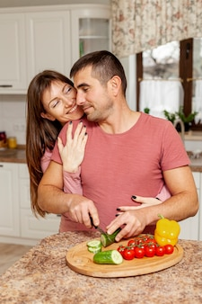 Man slicing vegetables embraced by his girlfriend