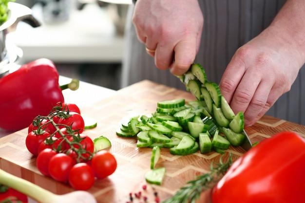 自宅でサラダ用の野菜をスライスする男