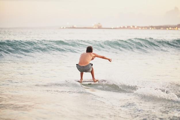 日没時にビーチで波に近づくためにスキムボードで滑る男
