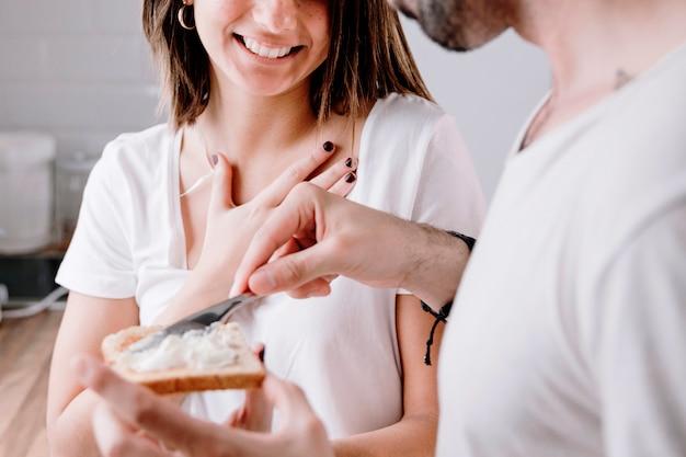 Uomo che spalma burro su pane tostato per donna