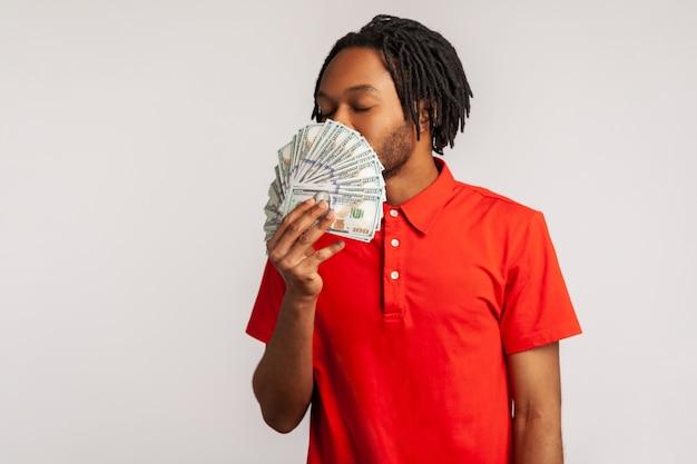 돈을 벌고 있는 달러 지폐의 냄새를 맡는 남자는 성공과 큰 이익, 부유한 삶, 돈에 대한 욕심을 즐깁니다.
