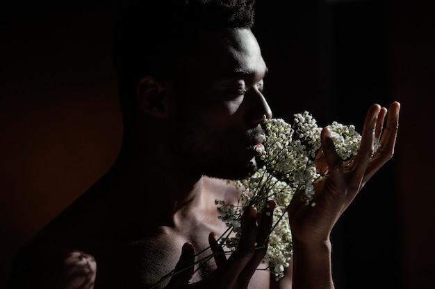 花のクローズアップのにおいがする男