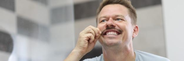 Мужчина улыбается и держит усы перед зеркалом
