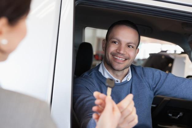 Человек улыбается, когда берет ключ автомобиля