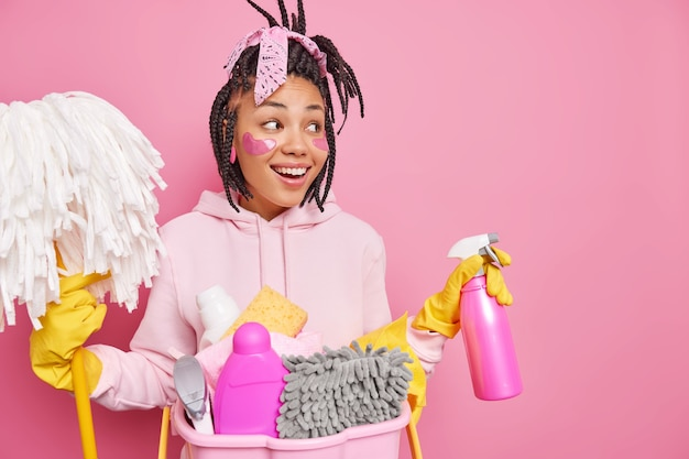Man smiles gladfully looks away applies collagen patches under eyes holds dispenser and mop stands near basket with cleaning detergents isolated on pink wall with copy space