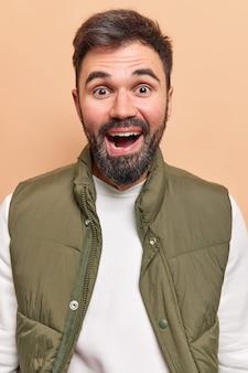 男性は幸せそうに笑い、前向きな表情を持って満足していると感じています。優れたニュースはベージュで隔離されたベストと白いジャンパーを着ています。