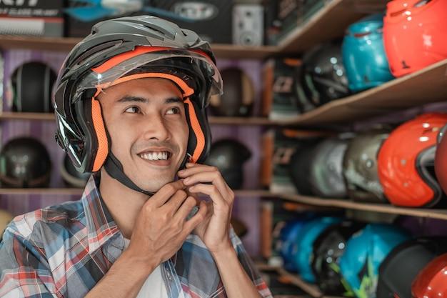 男はヘルメットのディスプレイラックにヘルメットを着用しながらバックルストラップを引っ掛けて微笑む