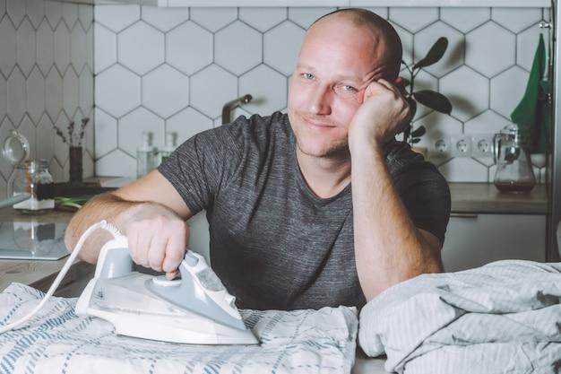 Мужчина улыбается гладит постельное белье, отец занимается домашними делами Premium Фотографии