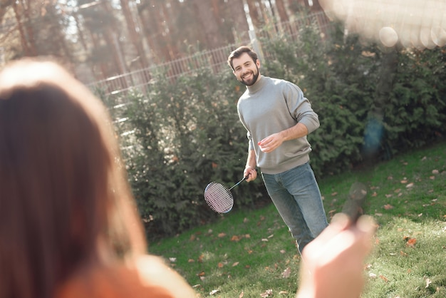 A man smiles and plays badminton with a girl.