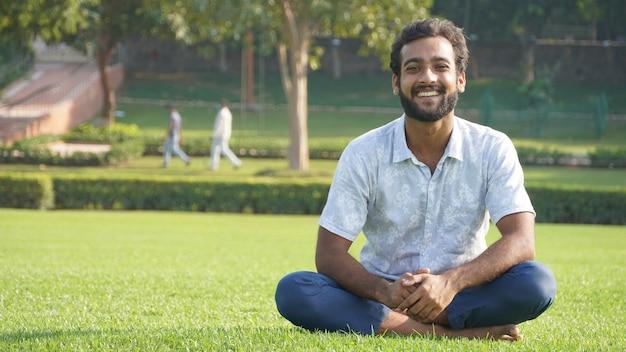 公園で瞑想の後に笑っている男