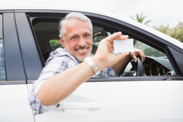 笑顔とカードを持っている男