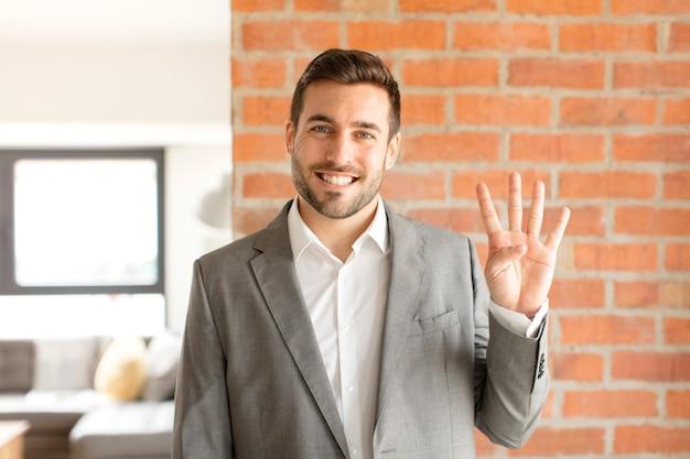 Мужчина улыбается и выглядит дружелюбно, показывает номер четыре или четвертый с рукой вперед, считает