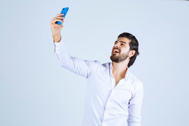 笑顔で青いスマートフォンで自分撮りをしている男