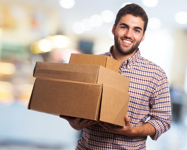 Man smiling carrying boxes