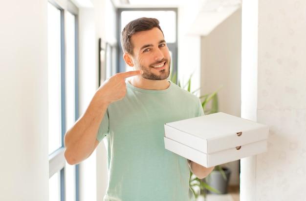 Мужчина уверенно улыбается, указывая на собственную широкую улыбку, позитивное, расслабленное, удовлетворенное отношение